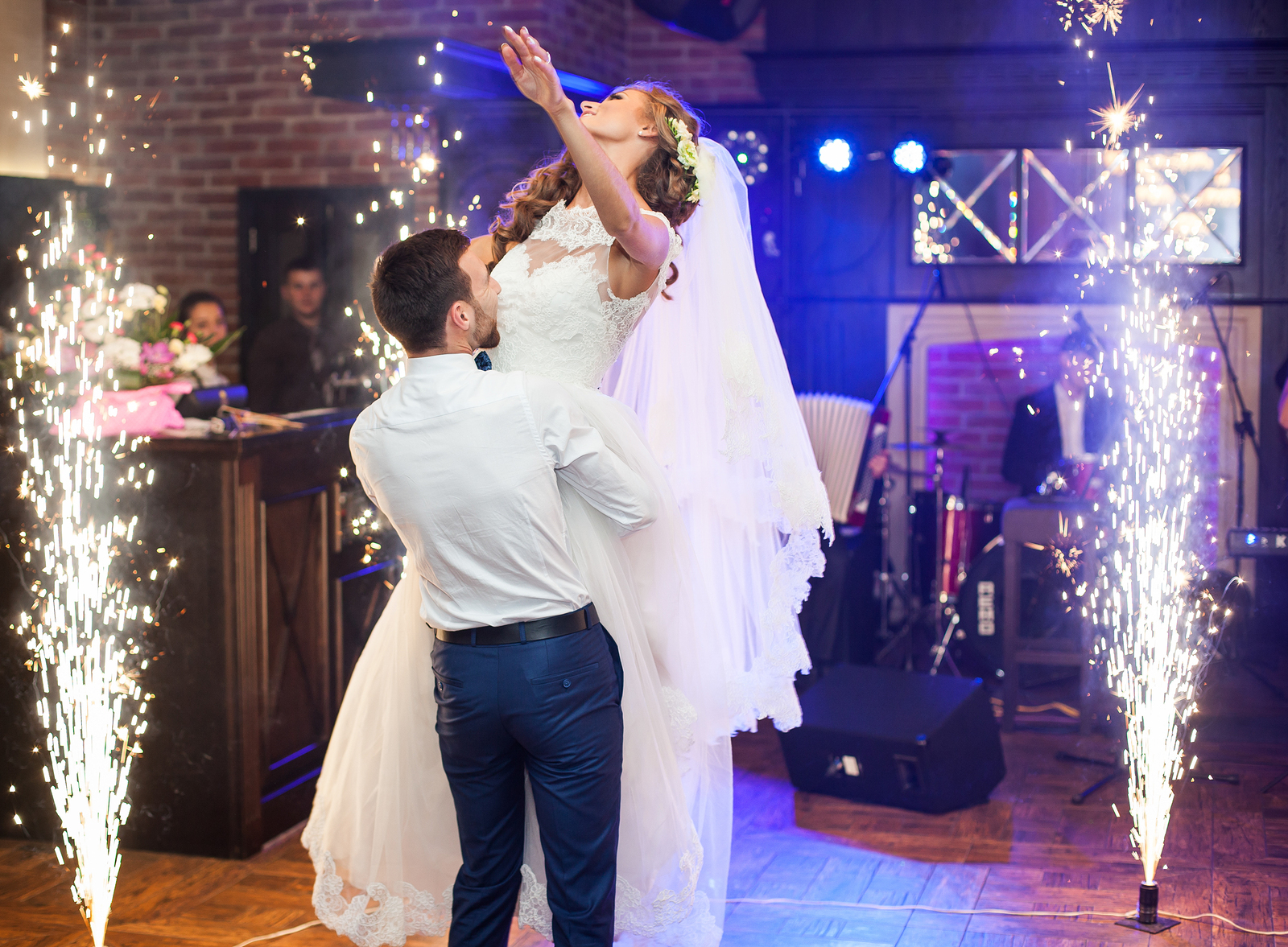 Beautiful newlywed couple first dance at wedding reception surrounded by smoke and blue lights amd sparks